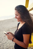 Adolescente joven mientras que usa el smartphone en la playa Foto de archivo libre de regalías