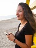 Adolescente joven mientras que usa el smartphone en la playa Imagenes de archivo