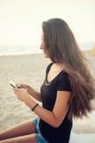 Adolescente joven mientras que usa el smartphone en la playa Foto de archivo