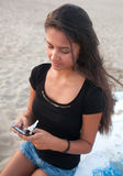 Adolescente joven mientras que usa el smartphone en la playa Imagen de archivo