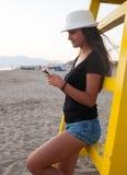 Adolescente joven mientras que usa el smartphone en la playa Fotos de archivo libres de regalías