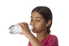 Adolescente joven que bebe el agua dulce de una botella Fotografía de archivo libre de regalías