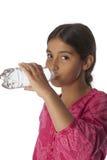 Adolescente joven que bebe el agua dulce de una botella Imagen de archivo