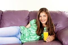 Adolescente joven que bebe el zumo de naranja Foto de archivo libre de regalías