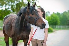 Adolescente joven que besa blando su caballo marrón preferido Foto de archivo