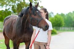 Adolescente joven que besa blando su caballo preferido de la castaña Imagen de archivo