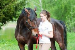 Adolescente joven que camina así como su caballo en delantera verde Foto de archivo libre de regalías