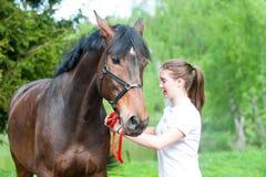 Adolescente joven que camina así como su caballo en delantera verde Imagenes de archivo