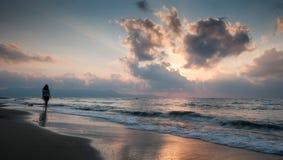 Adolescente joven que camina en una playa arenosa durante puesta del sol Fotografía de archivo