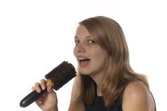 Adolescente joven que canta en su cepillo de pelo. Foto de archivo