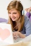 Adolescente joven que charla en el ordenador portátil Foto de archivo