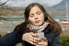 Adolescente joven que escucha la música en su teléfono Fotos de archivo