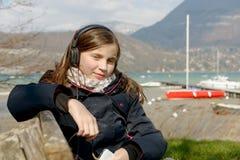 Adolescente joven que escucha la música en su teléfono Imagen de archivo libre de regalías