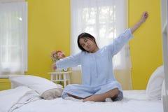 Adolescente joven que estira en cama Imagen de archivo