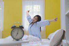 Adolescente joven que estira en cama Fotografía de archivo