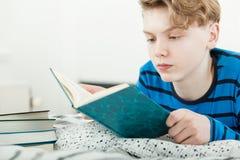 Adolescente joven que estudia en casa en su cama Foto de archivo libre de regalías