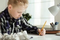 Adolescente joven que hace la preparación en el escritorio en hogar Imagen de archivo libre de regalías