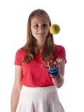 Adolescente joven que lanza una pelota de tenis en el aire Fotos de archivo