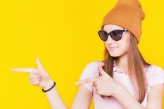 Adolescente joven que lleva un sombrero y las gafas de sol que señalan a Imágenes de archivo libres de regalías