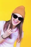 Adolescente joven que lleva un sombrero y las gafas de sol que señalan para vaciar Foto de archivo
