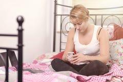 Adolescente joven que manda un SMS en su móvil Imagen de archivo libre de regalías