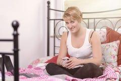 Adolescente joven que manda un SMS en su móvil Fotografía de archivo