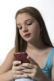 Adolescente joven que manda un SMS en su teléfono móvil Imágenes de archivo libres de regalías