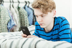 Adolescente joven que manda un SMS a un mensaje en un móvil Fotografía de archivo