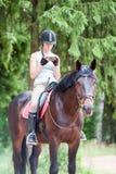 Adolescente joven que mira el smartphone que se sienta a caballo Fotografía de archivo libre de regalías