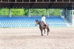 Adolescente joven que monta un caballo después de entrenar en arena Fotografía de archivo