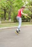 Adolescente joven que patina en las cuchillas del rodillo Imagen de archivo libre de regalías