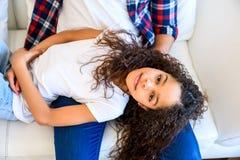 Adolescente joven que pone en el sofá Foto de archivo