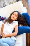 Adolescente joven que pone en el sofá Imágenes de archivo libres de regalías