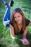Adolescente joven que pone en hierba Imágenes de archivo libres de regalías