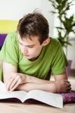 Adolescente joven que relaja en casa la lectura Imagenes de archivo