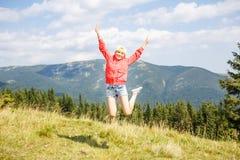 Adolescente joven que salta en montañas Imagenes de archivo
