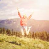 Adolescente joven que salta en montañas Imagen de archivo