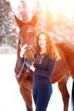 Adolescente joven que se coloca con el caballo en parque Imagenes de archivo