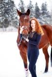 Adolescente joven que se coloca con el caballo en parque Foto de archivo