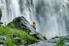 Adolescente joven que se coloca en la cascada cercana de piedra grande imágenes de archivo libres de regalías