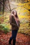 Adolescente joven que se coloca en un bosque en otoño Imagen de archivo libre de regalías
