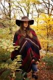 Adolescente joven que se coloca en un bosque en otoño Foto de archivo libre de regalías