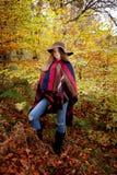 Adolescente joven que se coloca en un bosque en otoño Fotografía de archivo