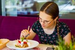 Adolescente joven que se divierte que come el helado en café Fotos de archivo libres de regalías