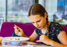 Adolescente joven que se divierte que come el helado en café Foto de archivo libre de regalías