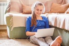 Adolescente joven que se divierte con el ordenador portátil en casa Imagen de archivo