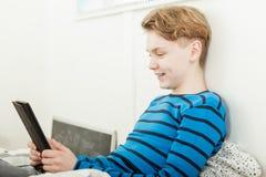 Adolescente joven que se relaja en cama con la tableta Fotos de archivo libres de regalías