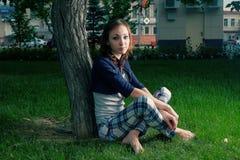 Adolescente joven que se sienta cerca de árbol en fresco Imagen de archivo