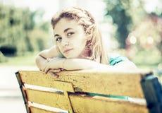 Adolescente joven que se sienta en el banco en parque Imagen de archivo