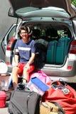 Adolescente joven que se sienta en el coche con los vidrios Fotos de archivo